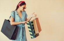 A smiling woman wearing a denim dress and a red headband looks down at her shopping bags